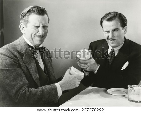 Two men squirting grapefruit juice at each other - stock photo