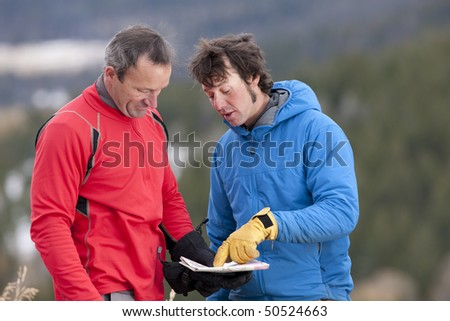 Two men stand and look down at a map together in the wilderness. One man is pointing at a spot on the map and talking. Horizontal format. - stock photo