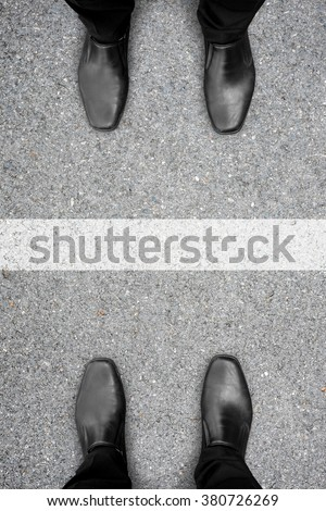Two men standing in front of each other like enemy, competent, rival or friends and white line between them - stock photo