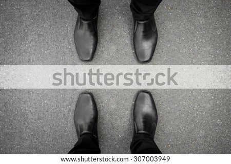 Two men standing on both side of the white line - stock photo