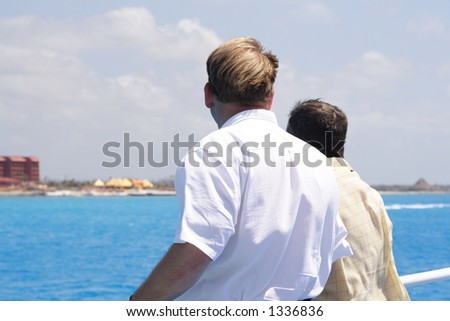 two men standing on the deck of a boat looking out at the shore