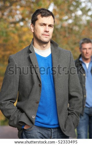 Two Men Standing Outside In Autumn Woodland - stock photo