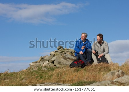 Two Men Stopping For Rest On Countryside Walk - stock photo