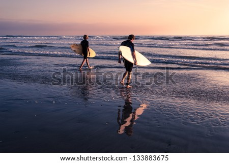 Two Men - Surfers in black diving suits. With old white and yellow surfboards. On the beach at sunset. - stock photo