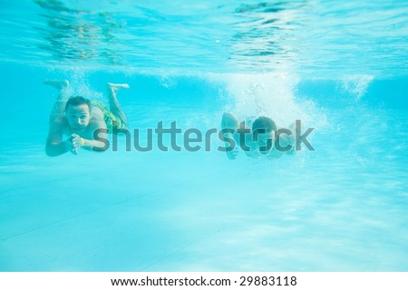 Two men swimming together under water in pool - stock photo