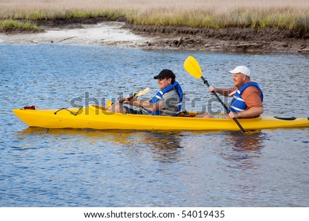 Two men take a kayak trip through the marshland. - stock photo