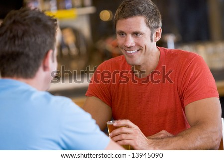 Two men talking over beer in a bar - stock photo