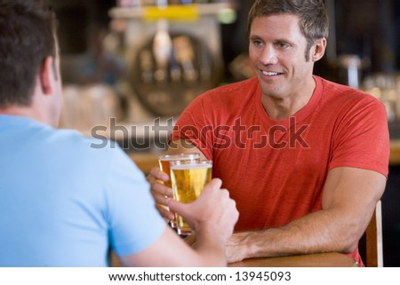 Two men toasting beer in a bar - stock photo