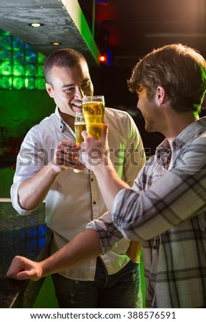 Two men toasting with glass of beer at bar counter in bar - stock photo