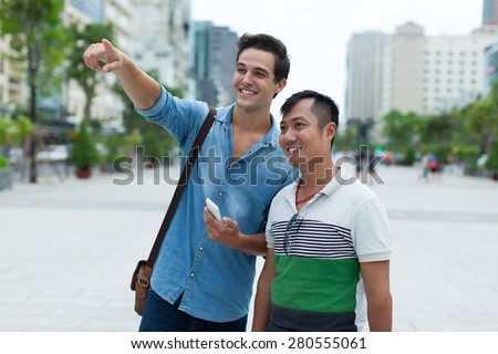 Two men tourists smile point finger sightseeing, asian mix race friends guys outdoor city street  - stock photo
