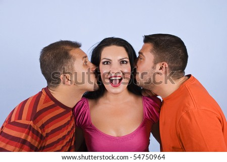Two men trying to kiss a woman and she is surprised and making a funny face on blue background - stock photo