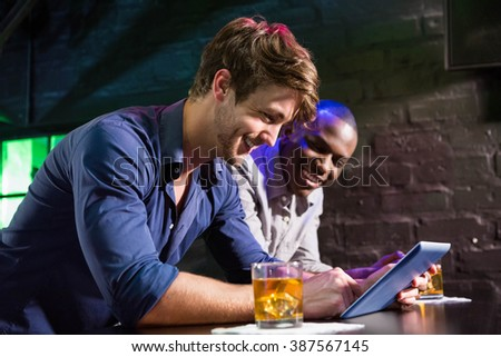 Two men using digital table while having whiskey at bar counter in bar - stock photo