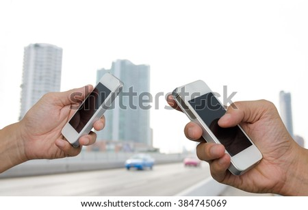 Two men using mobile smart phone with blurred background of big buildings and cityscape, communication concept, transaction concept. - stock photo