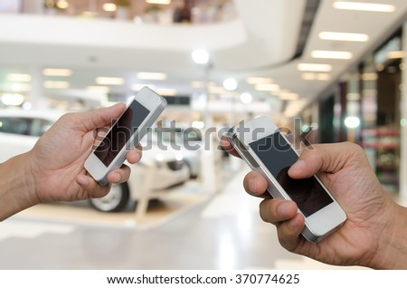 Two men using mobile smart phone with blurred background of new cars displayed in showroom, communication concept, transaction concept. - stock photo
