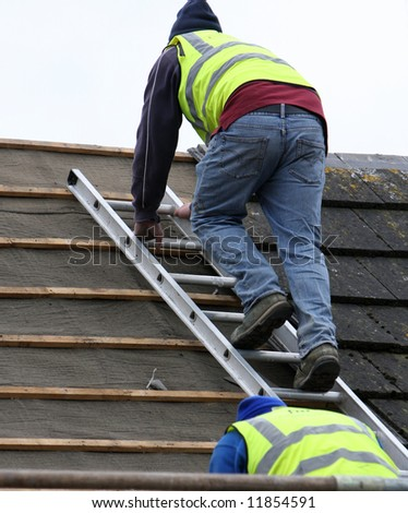 Two men using the roofing ladder to take slates off - stock photo