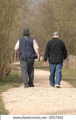 two men walking away from view along a country track