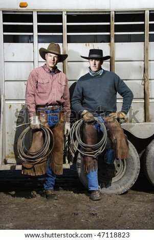 Two men wearing cowboy hats and leaning on the side of a livestock trailer. They are holding lariats. Vertical shot. - stock photo