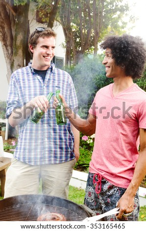Two men with beers toasting in front of a smoking barbecue, independence day party - stock photo