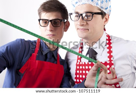 Two men with glasses and measuring tape. - stock photo
