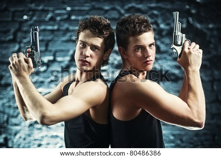 Two men with guns portrait. - stock photo