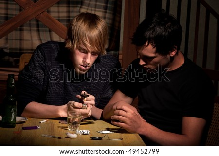 Two men with heroin cooking in a bent spoon - stock photo