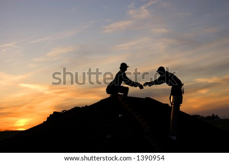 Two men working late on a roof - stock photo