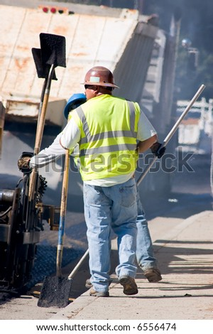 Two men working on a road repaving project. - stock photo