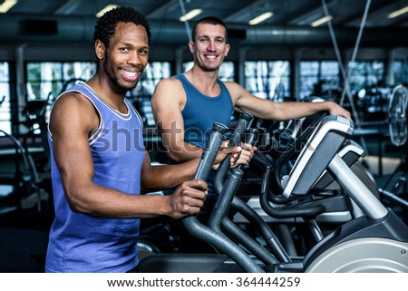 Two men working out together at the gym - stock photo