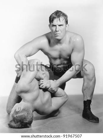 Two men wrestling with each other