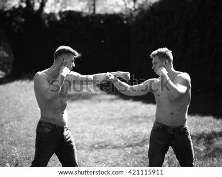 Two men young twins with sexy muscular body bare torso in jeans fight in match outside black and white on natural background - stock photo