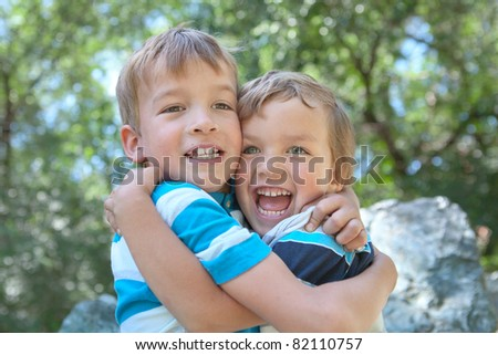 Two merry brothers hugging, in park - stock photo