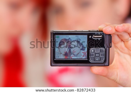Two merry girlfriends on photo camera screen - stock photo
