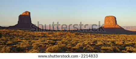 Two mesas are lit up by the rays of rising sun in Monument Valley, Navajo Nation, Utah. - stock photo