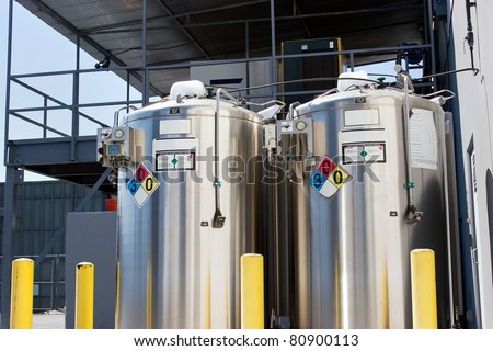 Two metal containers are label with placards and warning labels. - stock photo
