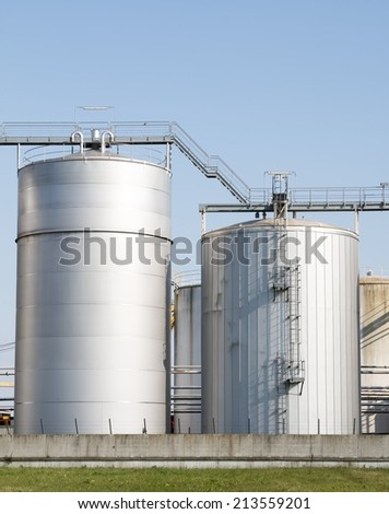 Two metal silos with stairs for food and agriculture on sky and green - stock photo