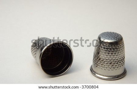two metallic thimbles on white background