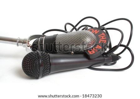 Two microphones and leads over white background