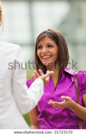 two mid adult business women talking outdoors. - stock photo