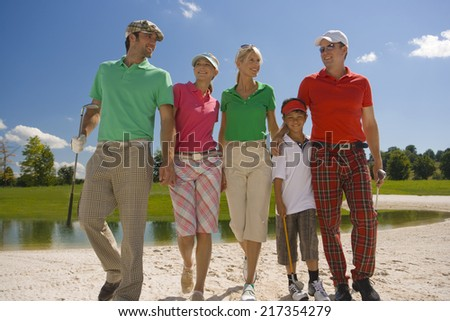 Two mid adult couples with a boy walking on the sand trap on a golf course - stock photo