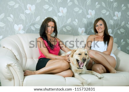 Two mid adult women with  labrador retriever  on sofa - stock photo