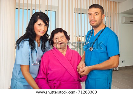 Two mid adults doctors holding elderly woman hands to help her to walk in a hospital room - stock photo