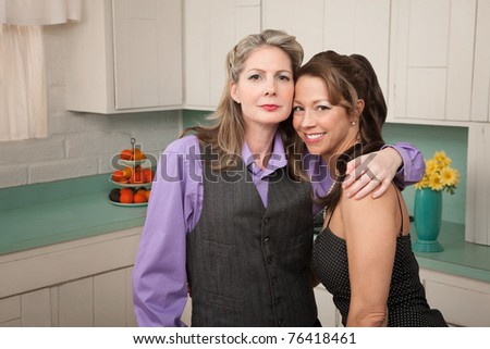 Two middle-aged friends hug in a kichen - stock photo