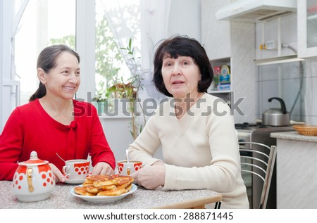 Two middle-aged  girlfriends drinking tea in   kitchen.  - stock photo
