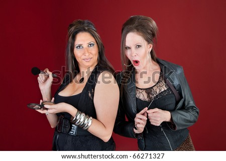 Two middle-aged ladies dressed in black prepare their makeup - stock photo