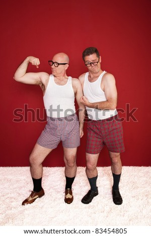 Two middle-aged men in boxers flex their muscles - stock photo
