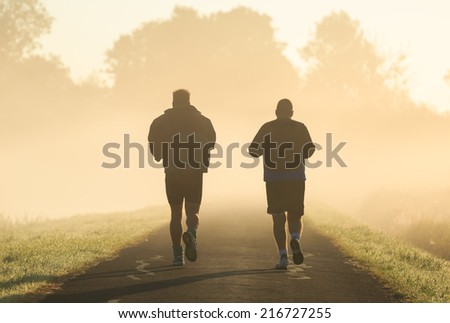 Two middle aged men running in the morning fog. - stock photo