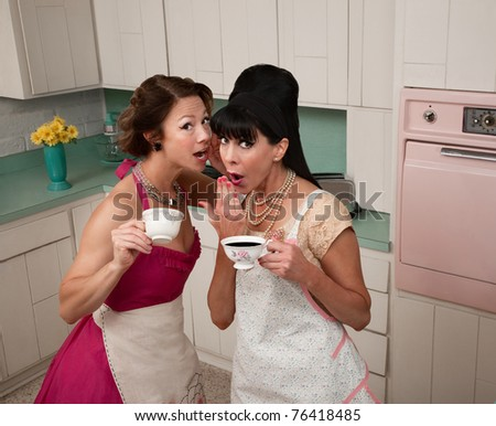 Two middle-aged retro styled women gosipping while having coffee - stock photo