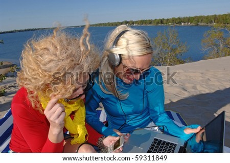 Two middle aged woman enjoy some computer time on the beach. - stock photo