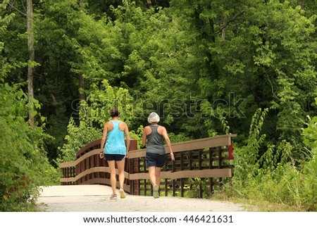 Two middle-aged women walking on a city trail; a bridge in the background - stock photo
