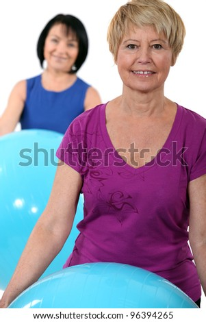 Two middle-aged women with gym balls - stock photo